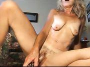 Een volwassen blondje masturbeert voor de camera